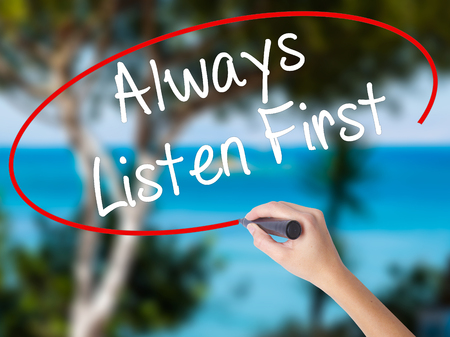 Woman Hand Writing Always Listen First with black marker on visual screen. Isolated on nature. Business concept. Stock Photo Stock Photo