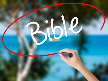 vangelo aperto: Woman Hand Writing Bible with black marker on visual screen. Isolated on nature. Business concept. Stock Photo