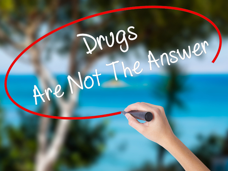 Woman Hand Writing Drugs Are Not The Answer with black marker on visual screen. Isolated on nature. Business concept. Stock Photo