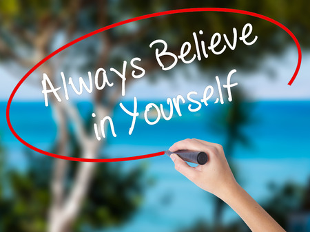 Woman Hand Writing Always Believe in Yourself with black marker on visual screen. Isolated on nature. Business concept. Stock Photo