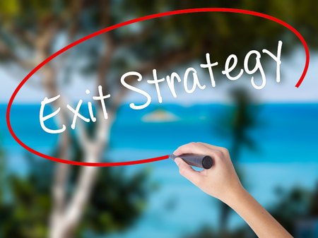 Woman Hand Writing Exit Strategy with black marker on visual screen. Isolated on nature. Business concept. Stock Photo