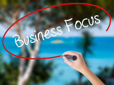Woman Hand Writing Business Focus with black marker on visual screen. Isolated on nature. Business concept. Stock Photo
