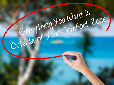 Woman Hand Writing Everything You Want is Outside of Your Comfort Zone with black marker on visual screen. Isolated on nature. Business concept. Stock Photo