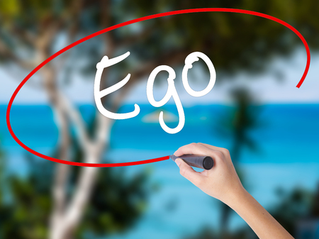 Woman Hand Writing Ego with black marker on visual screen. Isolated on nature. Business concept. Stock Photo Stock Photo