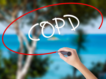 alveolos: Woman Hand Writing COPD with black marker on visual screen. Isolated on nature. Business concept. Stock Photo