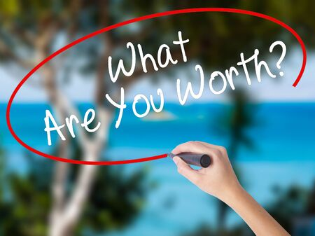Woman Hand Writing What Are You Worth? with black marker on visual screen. Isolated on nature. Business concept. Stock Photo Stock Photo