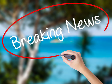 proclaim: Woman Hand Writing Breaking News with black marker on visual screen. Isolated on nature. Business concept. Stock Photo