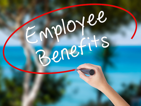 Woman Hand Writing Employee Benefits with black marker on visual screen. Isolated on nature. Business concept. Stock Photo Stock Photo