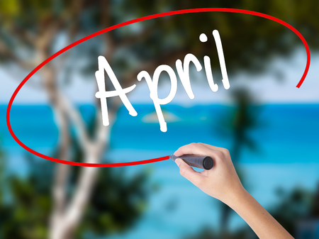 Woman Hand Writing  April  with black marker on visual screen. Isolated on nature. Business concept. Stock Photo Stock Photo