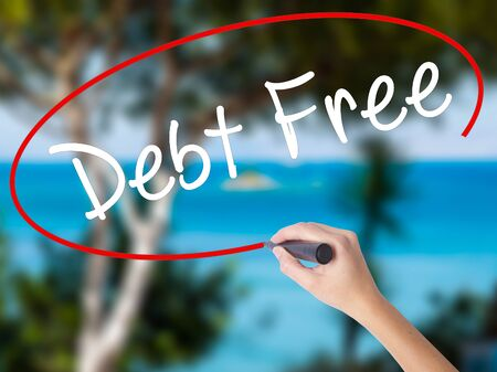 Woman Hand Writing Debt Free with black marker on visual screen. Isolated on nature. Business concept. Stock Photo