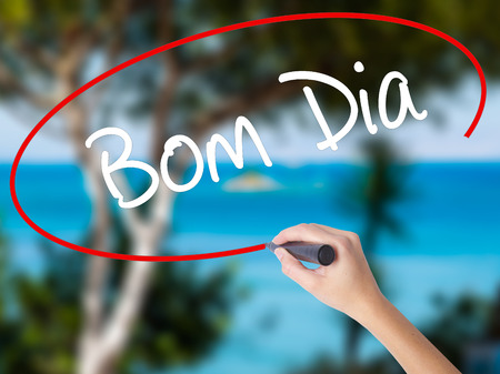 "Woman Hand Writing ""Bom Dia"" (In portuguese - Good Morning)  with black marker on visual screen. Isolated on nature. Business concept. Stock Photo"
