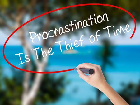 Woman Hand Writing  Procrastination Is The Thief of Time with black marker on visual screen. Isolated on nature. Business concept. Stock Photo Stock Photo