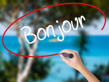 Woman Hand Writing Bonjour  (Good Morning in French) with black marker on visual screen. Isolated on nature. Business concept. Stock Photo Stock Photo