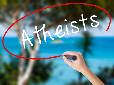 Woman Hand Writing Atheists with black marker on visual screen. Isolated on nature. Business concept. Stock Photo