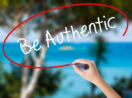 Woman Hand Writing Be Authentic with black marker on visual screen. Isolated on nature. Business concept. Stock Photo