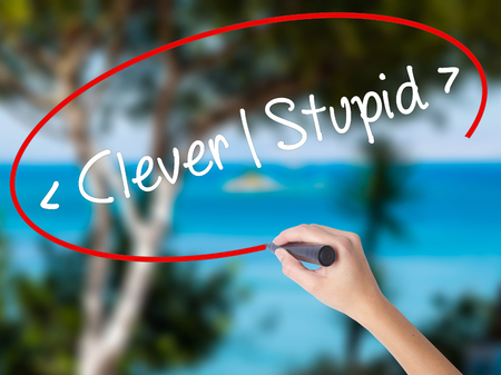 stupidity: Woman Hand Writing Clever - Stupid with black marker on visual screen. Isolated on nature. Business concept. Stock Photo Stock Photo