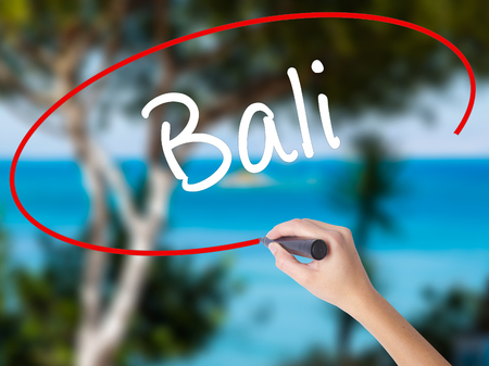 Woman Hand Writing Bali  with black marker on visual screen. Isolated on nature. Business concept. Stock Photo