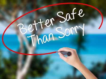 Woman Hand Writing Better Safe Than Sorry with black marker on visual screen. Isolated on nature. Business concept. Stock Photo