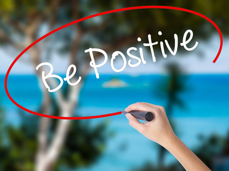 Woman Hand Writing Be Positive  with black marker on visual screen. Isolated on nature. Business concept. Stock Photo