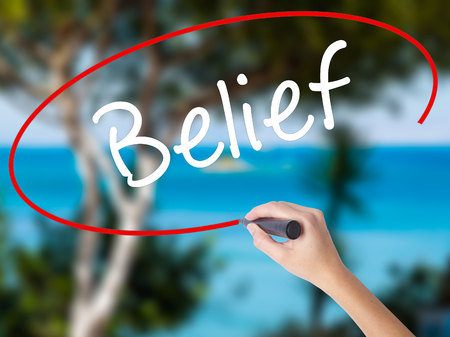 Woman Hand Writing Belief with black marker on visual screen. Isolated on nature. Business concept. Stock Photo