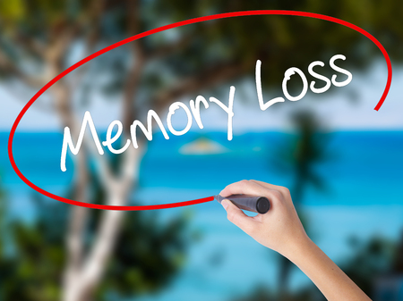 Woman Hand Writing Memory Loss with black marker on visual screen. Isolated on nature. Business concept. Stock Photo Stock Photo