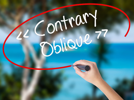 contrary: Woman Hand Writing Contrary - Oblique with black marker on visual screen. Isolated on nature. Business concept. Stock Photo