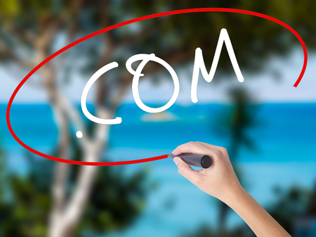 Woman Hand Writing .COM with black marker on visual screen. Isolated on nature. Business concept. Stock Photo