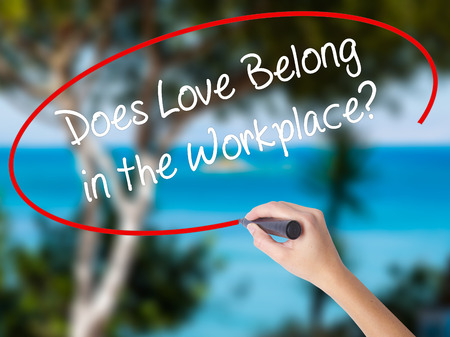 Woman Hand Writing Does Love Belong in the Workplace? with black marker on visual screen. Isolated on nature. Business concept. Stock Photo Stock Photo