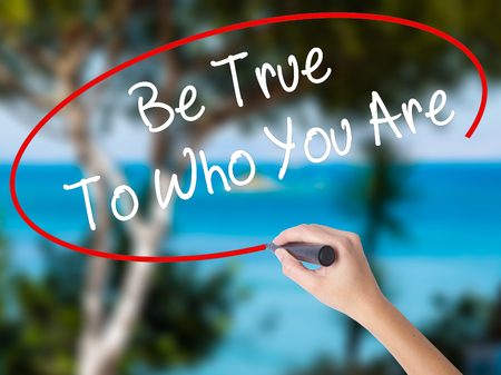 true self: Woman Hand Writing Be True To Who You Are with black marker on visual screen. Isolated on nature. Business concept. Stock Photo