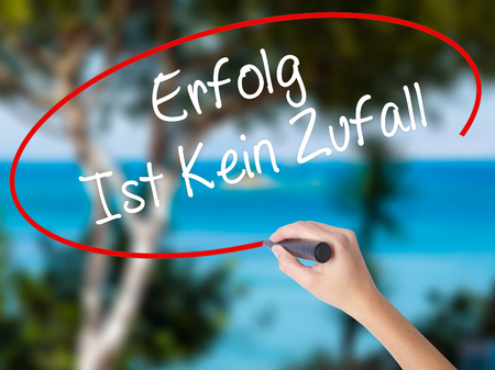 Woman Hand Writing Erfolg Ist Kein Zaufall (Success Is No Accident in German) with black marker on visual screen. Isolated on nature. Business concept. Stock Photo