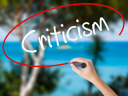 criticism: Woman Hand Writing Criticism with black marker on visual screen. Isolated on nature. Business concept. Stock Photo