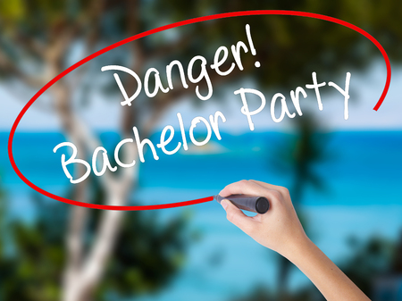 strip club: Woman Hand Writing Danger! Bachelor Party with black marker on visual screen. Isolated on nature. Business concept. Stock Photo Stock Photo