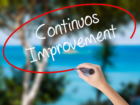 constant: Woman Hand Writing Continuos Improvement with black marker on visual screen. Isolated on nature. Business concept. Stock Photo