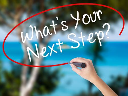 Woman Hand Writing Whats Your Next Step? with black marker on visual screen. Isolated on nature. Travel technology, internet concept. Stock Image