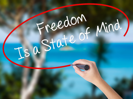 Woman Hand Writing Freedom Is a State of Mind with black marker on visual screen. Isolated on nature. Business concept. Stock Photo