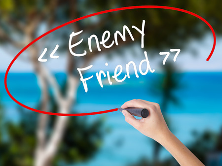 Woman Hand Writing Enemy - Friend with black marker on visual screen. Isolated on nature. Business concept. Stock Photo
