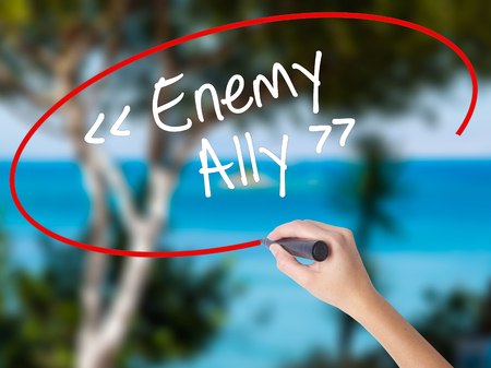 interdependence: Woman Hand Writing Enemy - Ally with black marker on visual screen. Isolated on nature. Business concept. Stock Photo Stock Photo