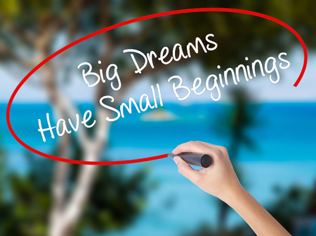 Woman Hand Writing Big Dreams Have Small Beginnings with black marker on visual screen. Isolated on nature. Business concept. Stock Photo