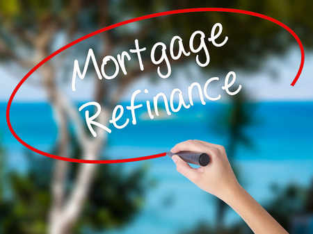 Woman Hand Writing Mortgage Refinance with black marker on visual screen. Isolated on nature. Business concept. Stock Photo