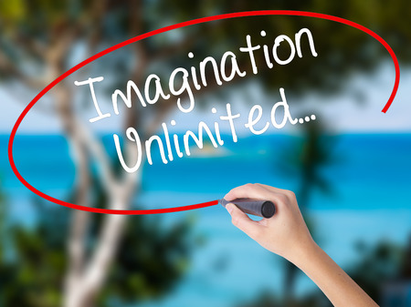Woman Hand Writing Imagination Unlimited... with black marker on visual screen. Isolated on nature. Business concept. Stock Photo
