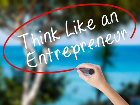 Woman Hand Writing Think Like an Entrepreneur with black marker on visual screen. Isolated on nature. Business concept. Stock Photo Stock Photo