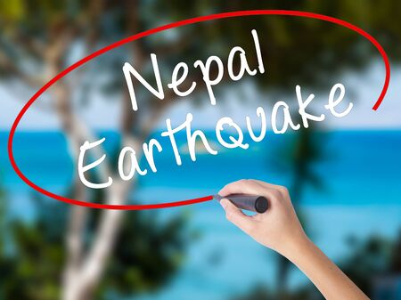 quake: Woman Hand Writing Nepal Earthquake with black marker on visual screen. Isolated on nature. Business concept. Stock Photo Stock Photo