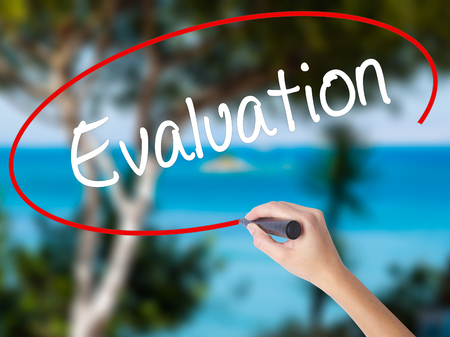 Woman Hand Writing Evaluation with black marker on visual screen. Isolated on nature. Business concept. Stock Photo