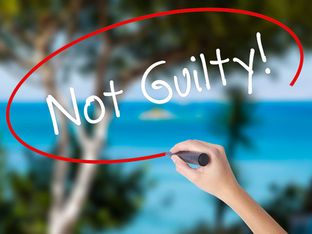 Woman Hand Writing NOT GUILTY with black marker on visual screen. Isolated on nature. Business concept. Stock Photo