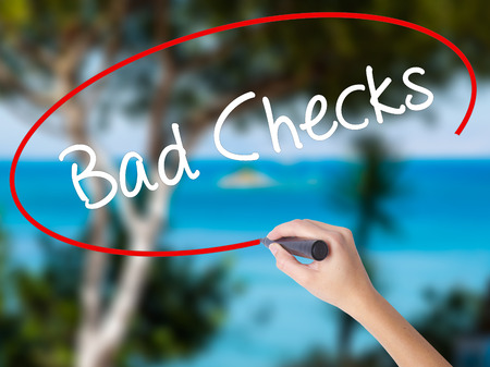 Woman Hand Writing Bad Checks with black marker on visual screen. Isolated on nature. Business concept. Stock Photo Stock Photo