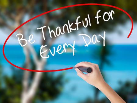 Woman Hand Writing Be Thankful for Every Day   with black marker on visual screen. Isolated on nature. Business concept. Stock Photo