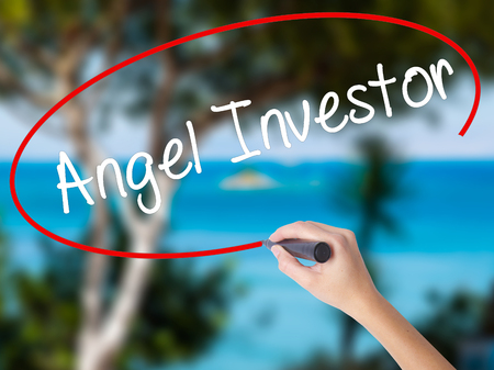 Woman Hand Writing Angel Investor with black marker on visual screen. Isolated on nature. Business concept. Stock Photo