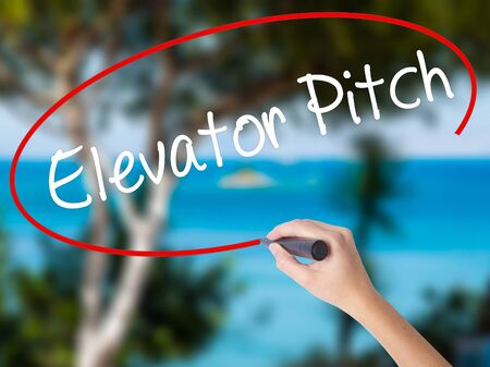 business pitch: Woman Hand Writing Elevator Pitch with black marker on visual screen. Isolated on nature. Business concept. Stock Photo
