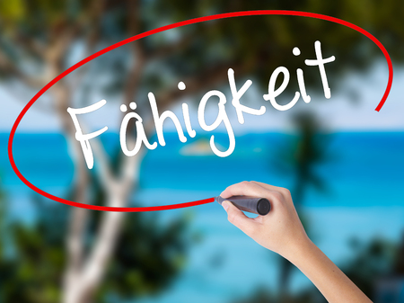 Woman Hand Writing Fahigkeit (Ability in German) with black marker on visual screen. Isolated on nature. Business concept. Stock Photo Stock Photo