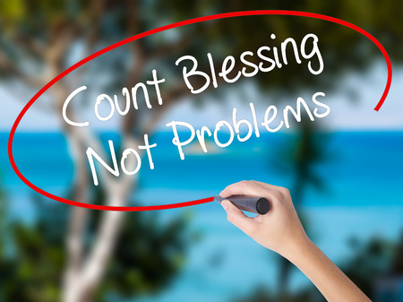 Woman Hand Writing Count Blessing Not Problems with black marker on visual screen. Isolated on nature. Business concept. Stock Photo